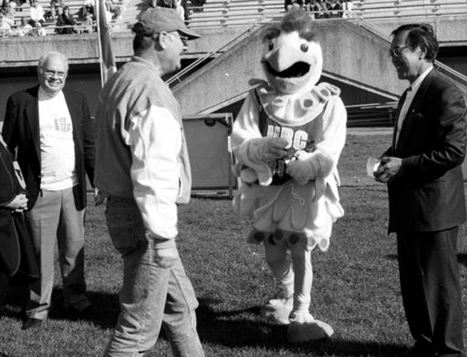 "David Strangway, far left, and Robert ""Bob"" Lee, right, at Thunderbird Stadium in 1994. Strangway and Lee were instrumental in shifting UBC's mission from one focused on educating the masses to one focused on raising money and becoming an elite institution."