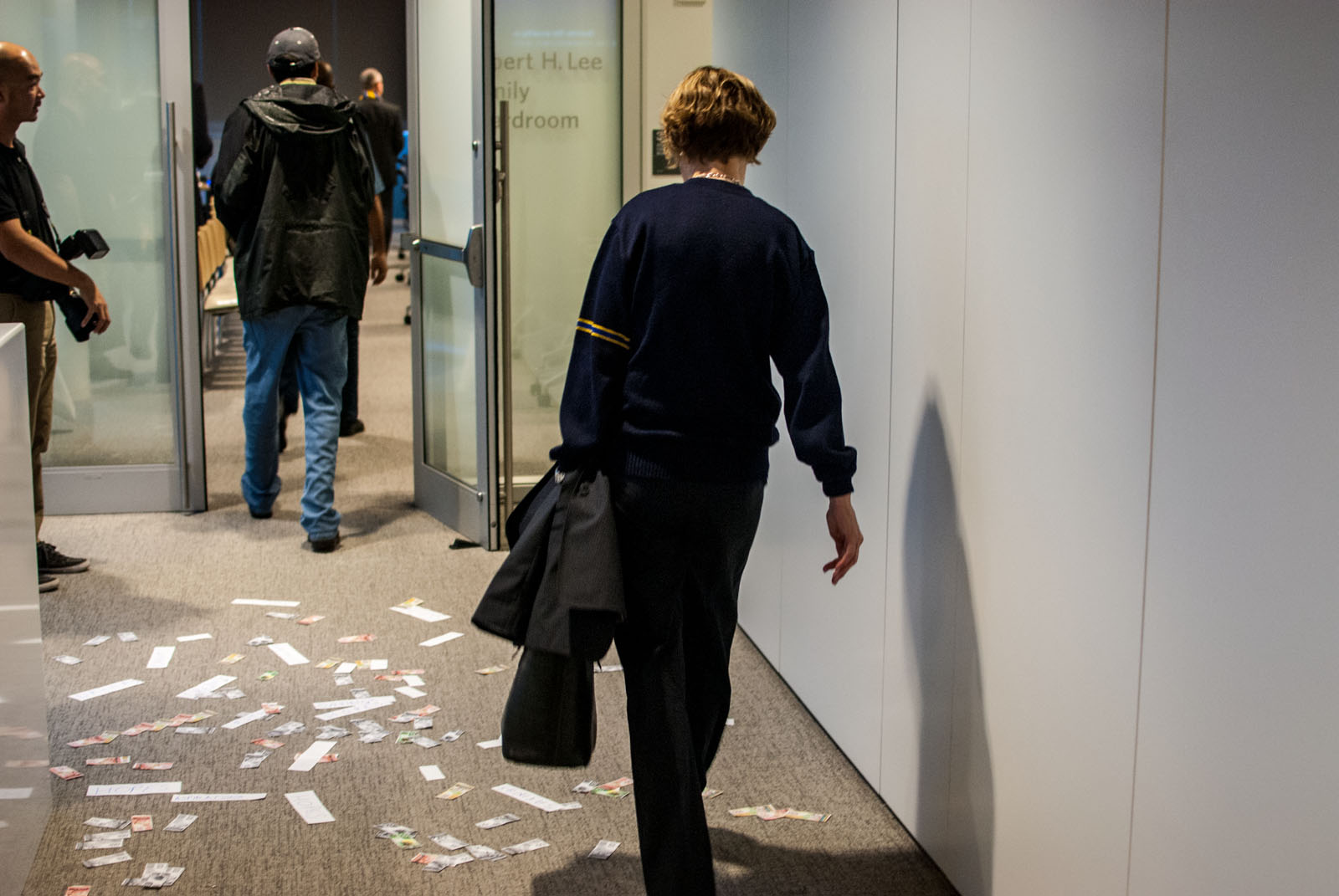 "President Martha Piper walks over fake money and slips of paper with the words ""hopes"" and ""dreams"" written on them, placed there by students before the meeting."