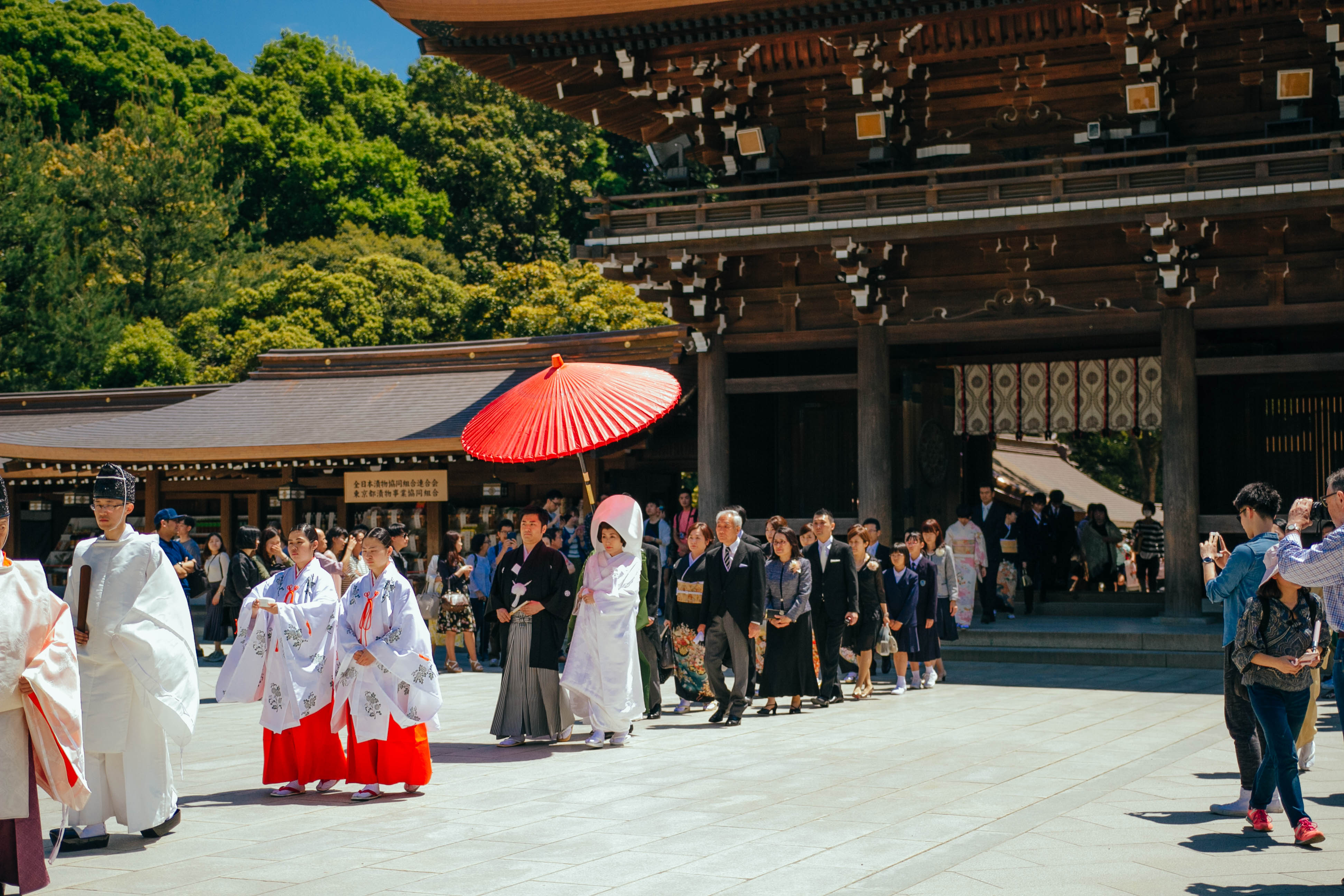 The wedding party donned traditional clothing, with the bride and groom being shaded from the intense sun by a bright red umbrella.
