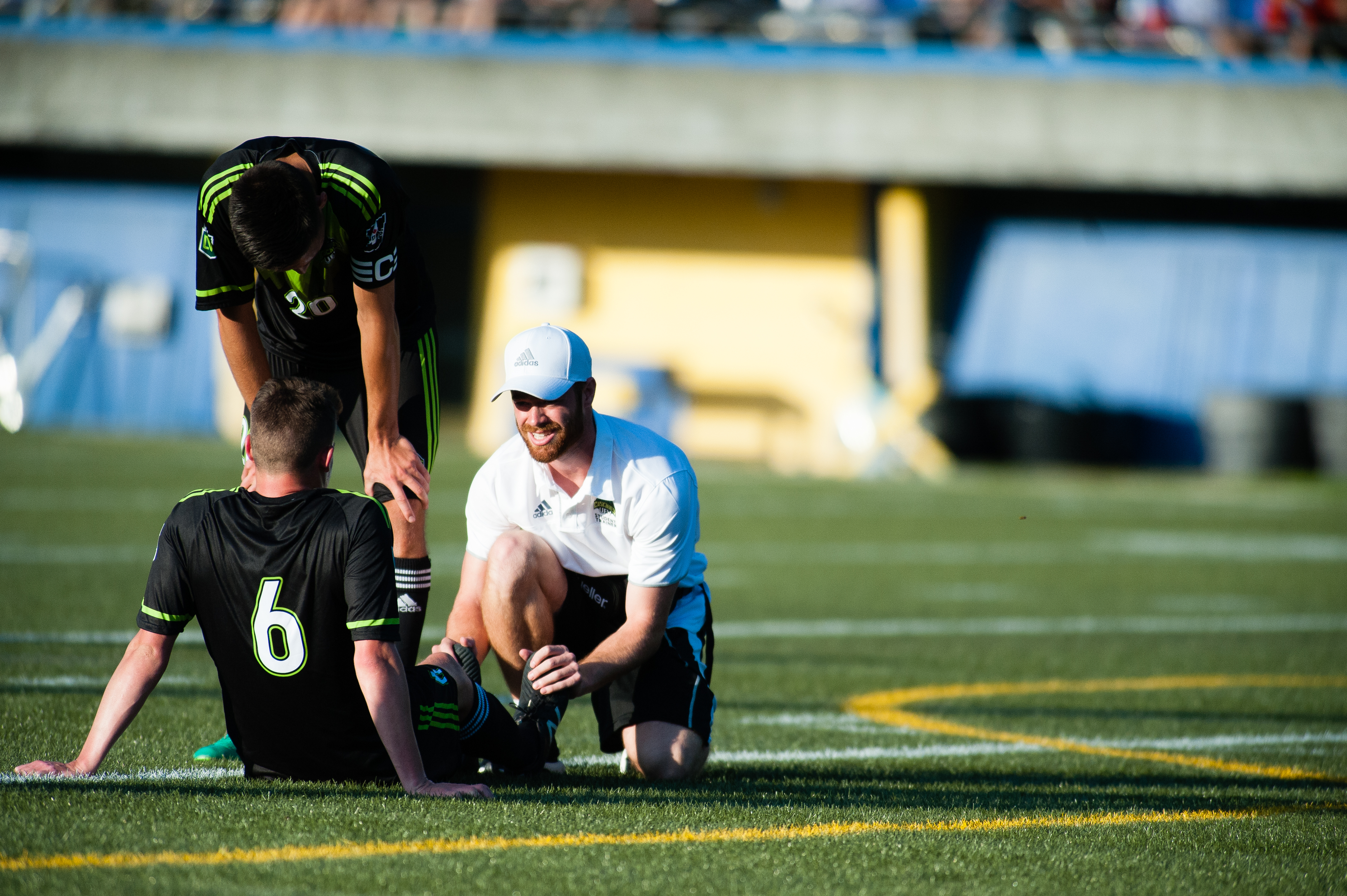 A trainer helps Cascades midfielder Spencer Williams after an injury in the first half. Williams later left the stadium on crutches.