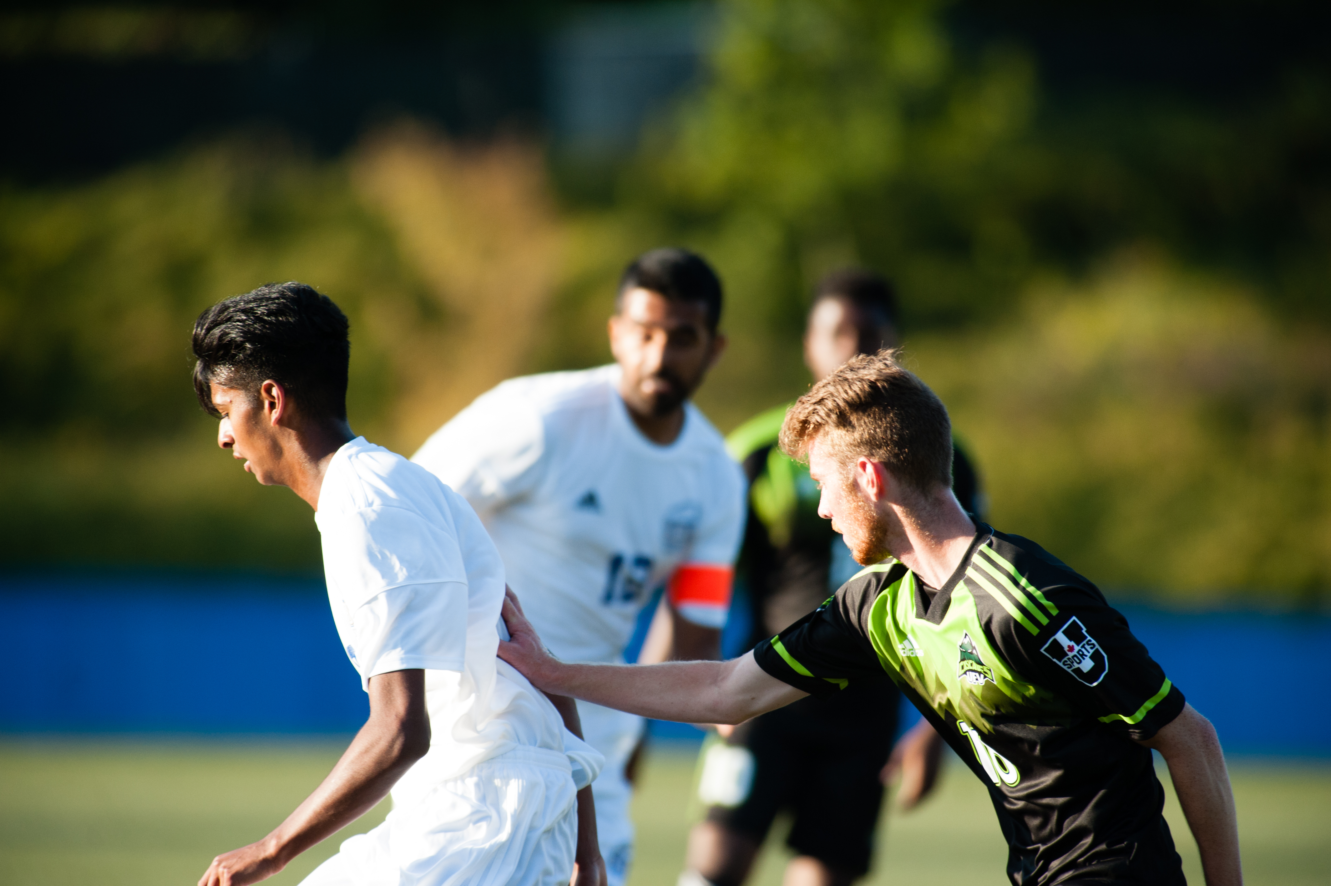 Cascades midfielder Brady Weir defends while UBC's Zach Verhoven receives a free kick.