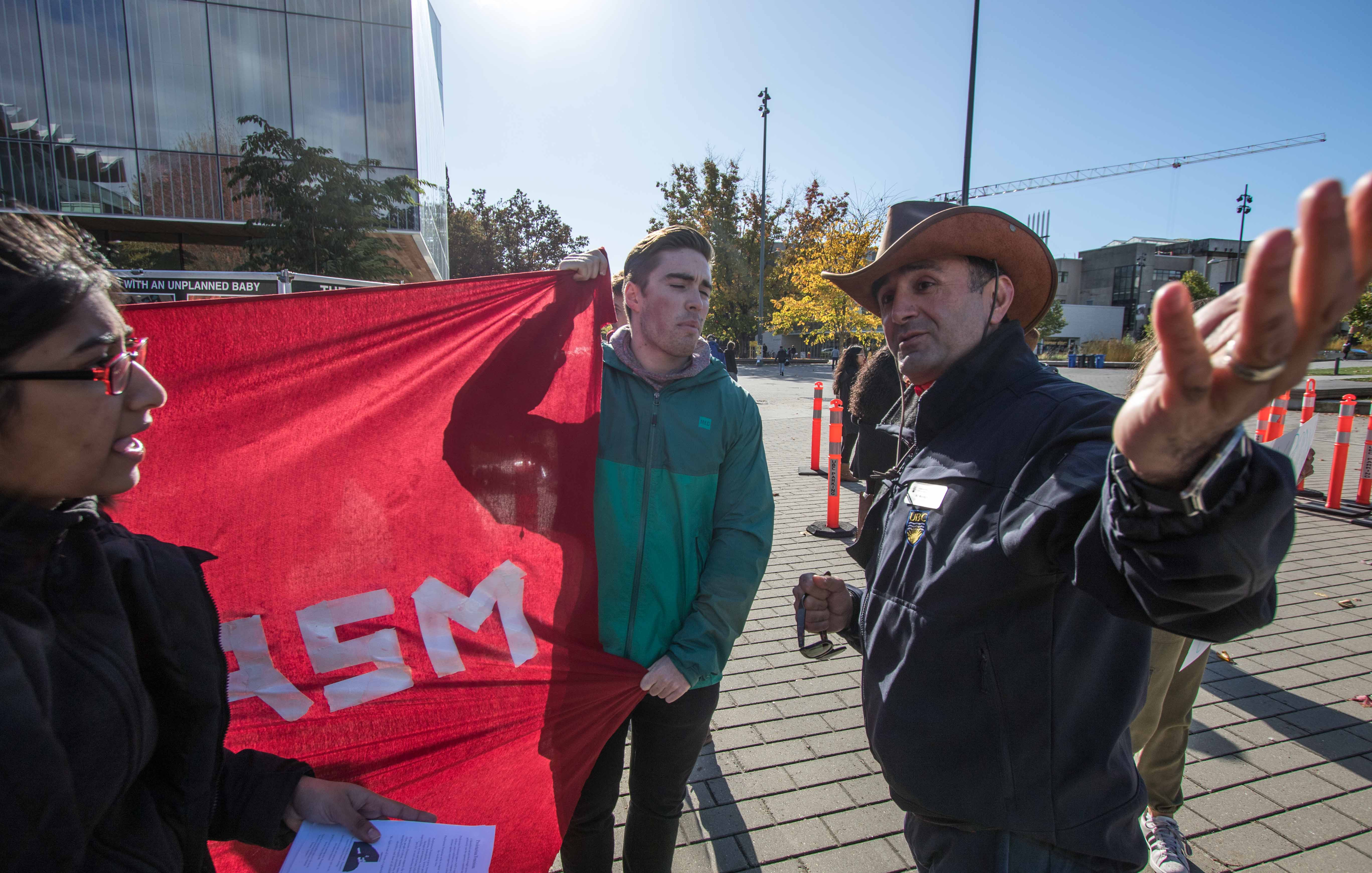 A UBC Security officer (right) gestures to the designated counter-protest zone.