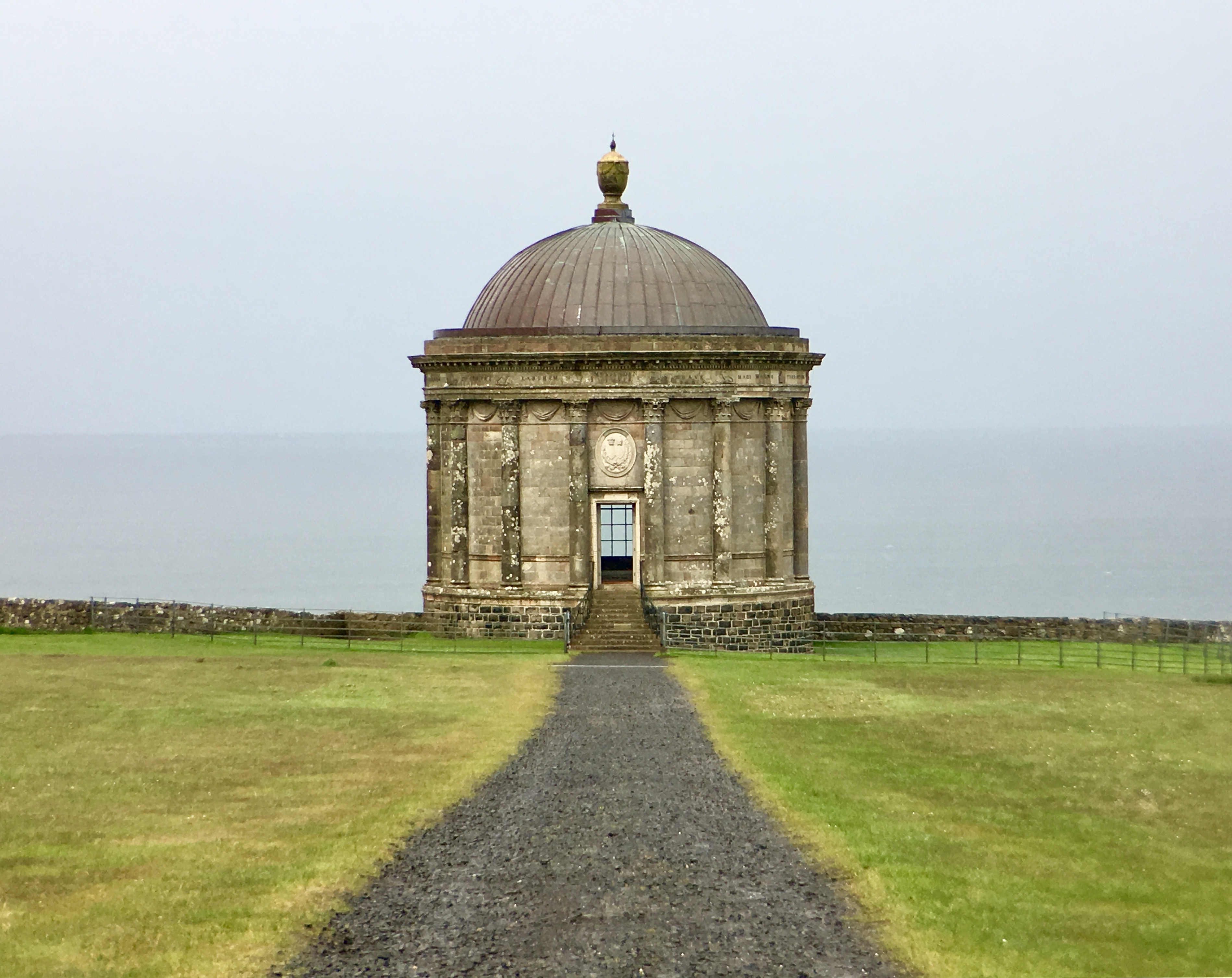 The Mussenden Temple stands on the edge of its cliff, appearing to be moments away from tumbling into the sea.