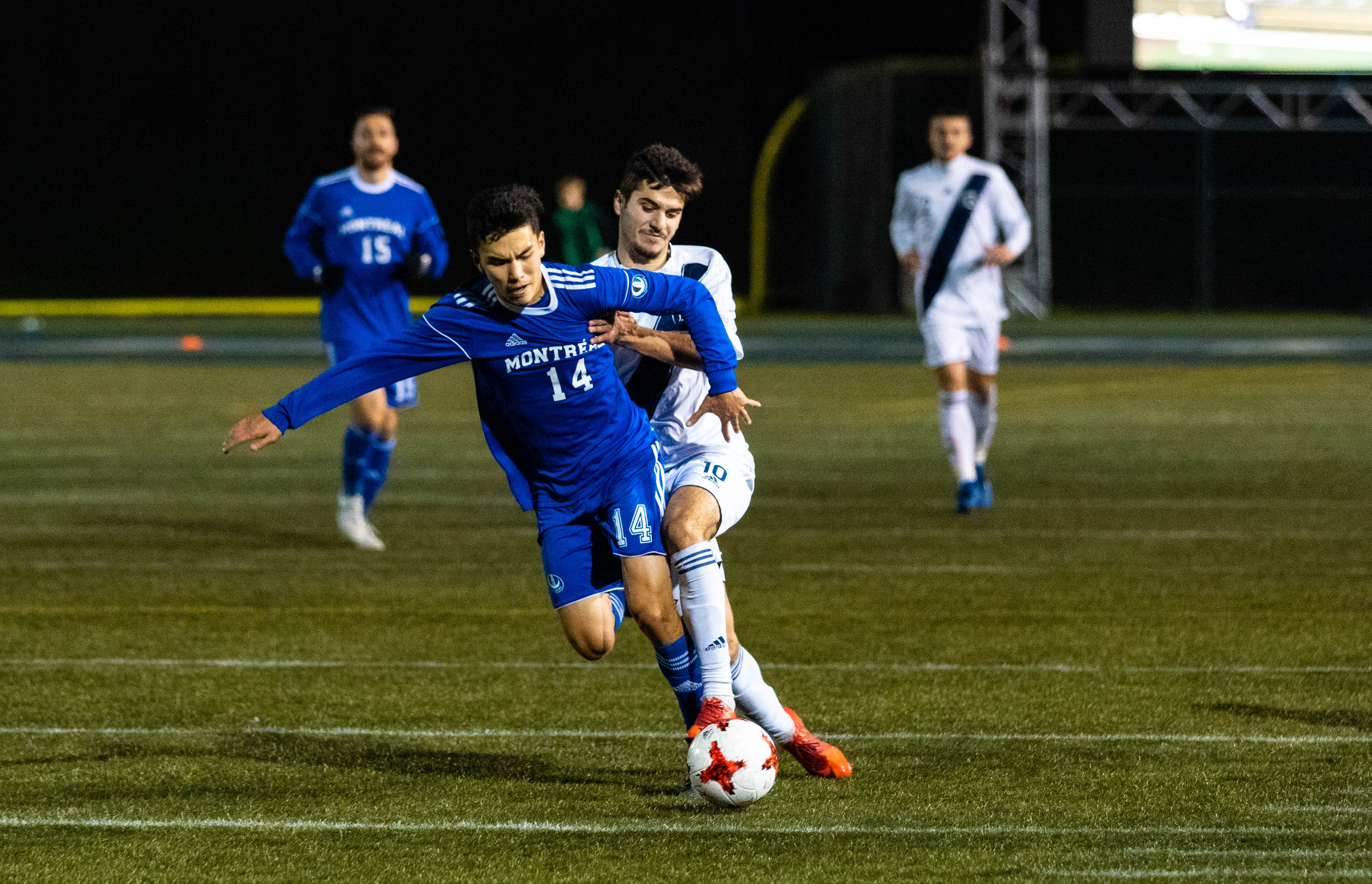 Trinity's Dominic Poletto tussles for the ball against Montreal's Pierre Lamothe.