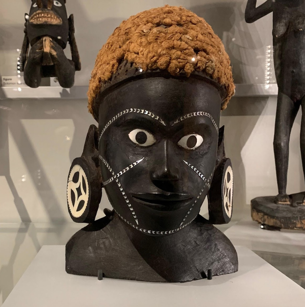 The black pigment of the sculpture is contrasted by the vibrant colour of her hair and the silver markings on her face.