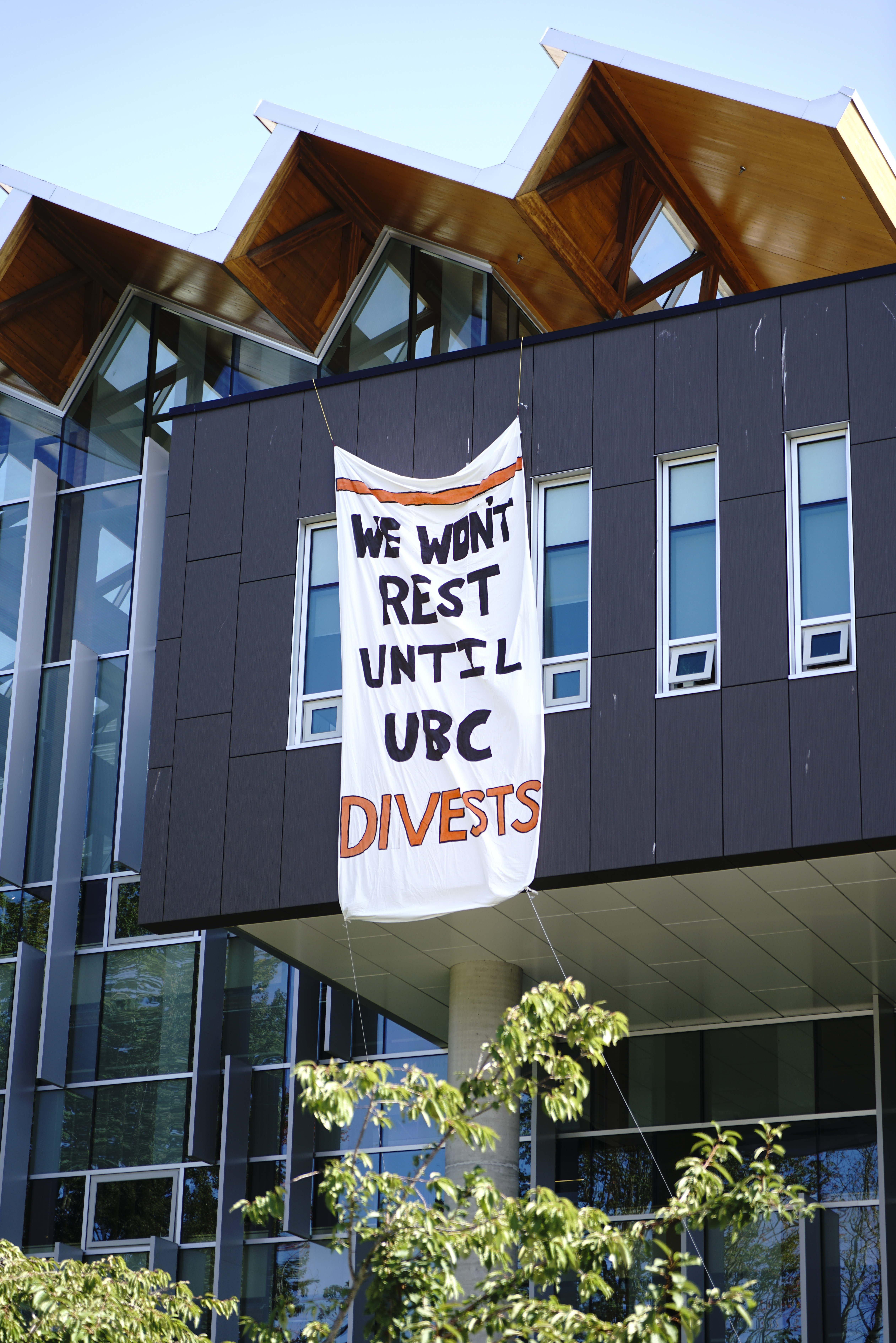 Climate Stike participants hang a banner over the Nest calling on UBC to divest from fossil fuels.