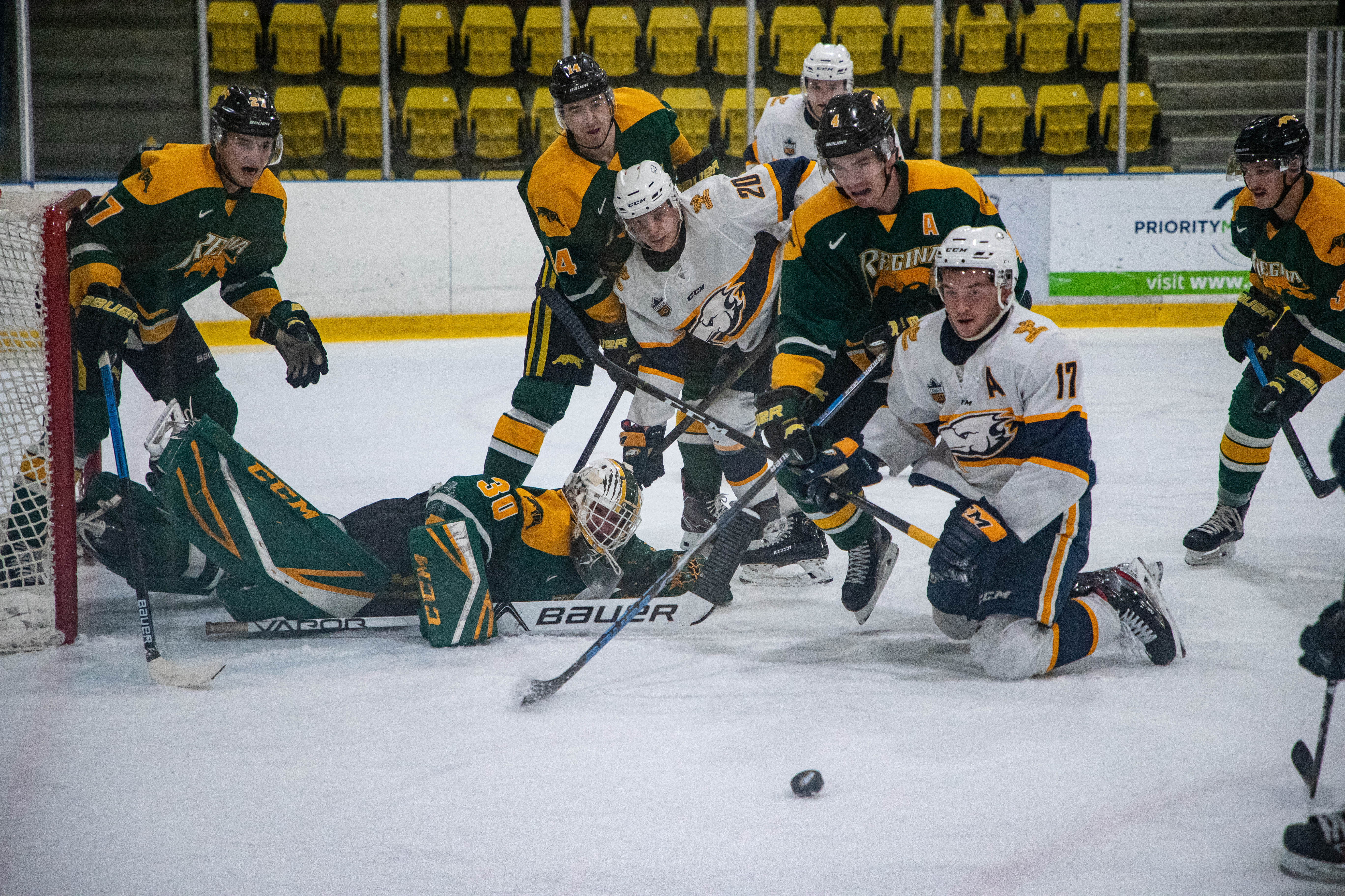 Players scramble for the puck in front of the Regina goal.