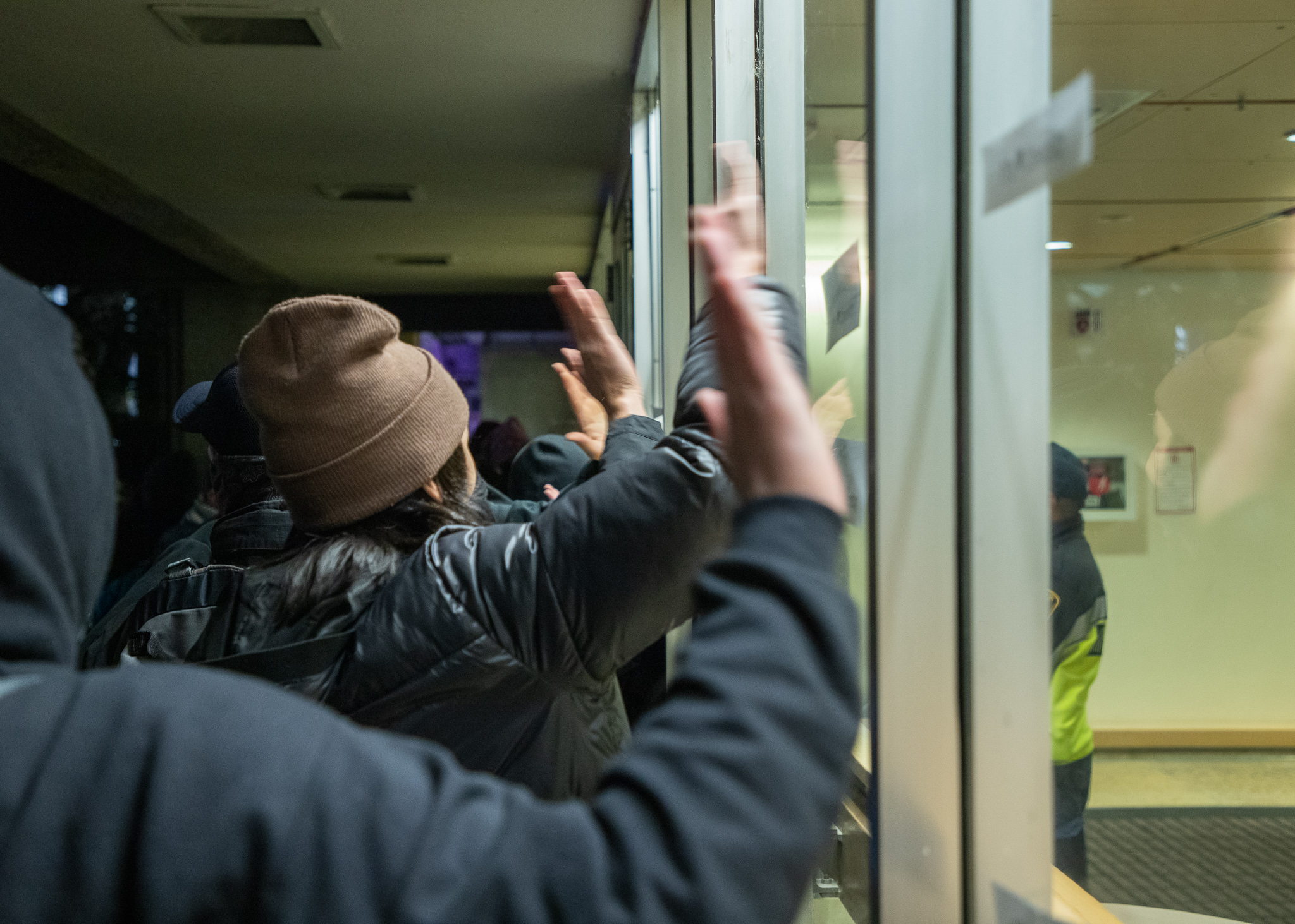 The protesters clustered around the entrance, chanting and beating the windows to disrupt the talk.