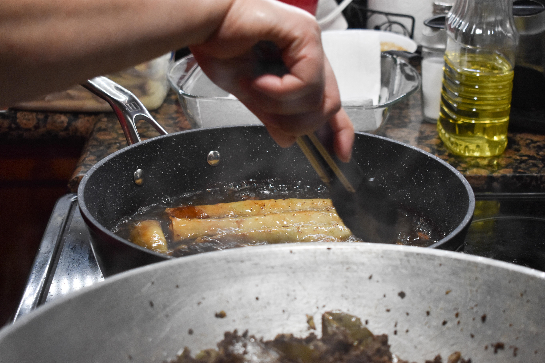 Alindogan's mother pan fries lumpia in their family kitchen.