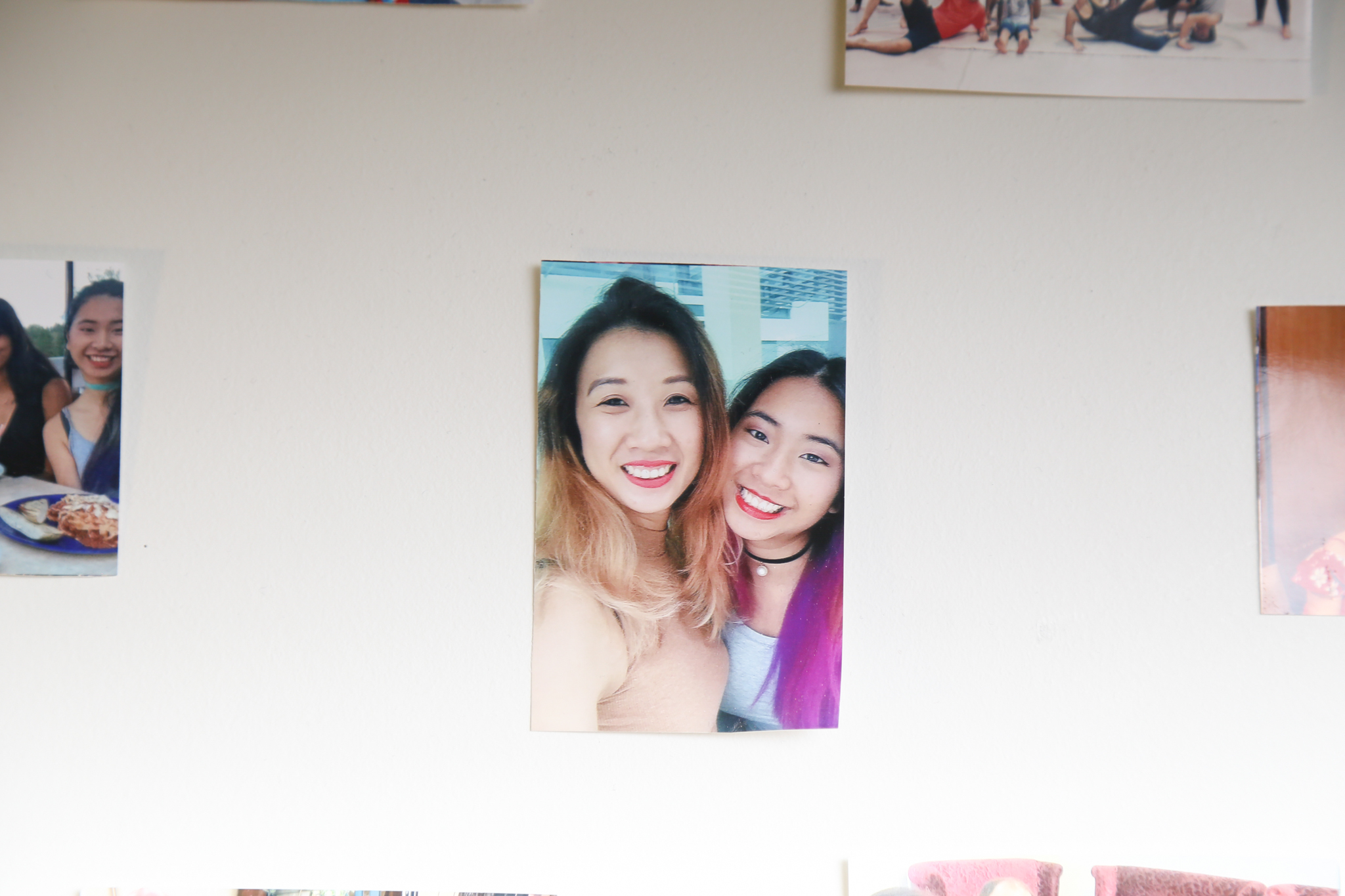A photo of Lee and her sister among a photo wall of friends and family in Lee's dorm room.