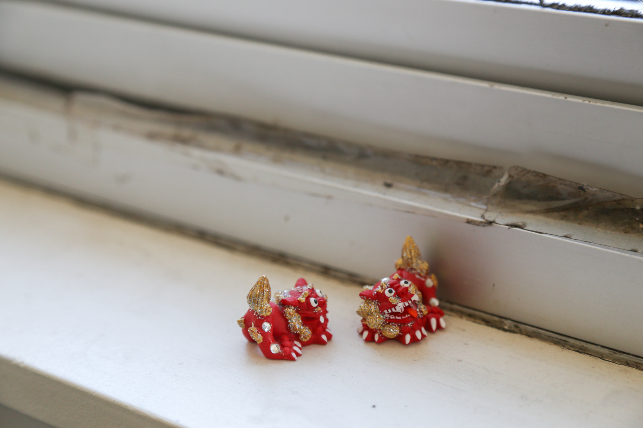 Two miniature lion figurines dance on Lee's window sill, a reminder of a trip to Japan with her family.